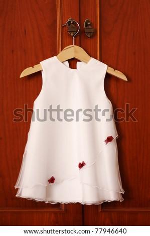 Children's white elegant dress hanging on hanger. - stock photo