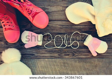 Children's winter clothes: warm scarf, mittens, boots. 2016 year written laces of children's mittens on old wooden background. Toned image   - stock photo