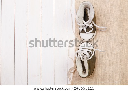 Children's winter shoes on burlap and wooden background - stock photo