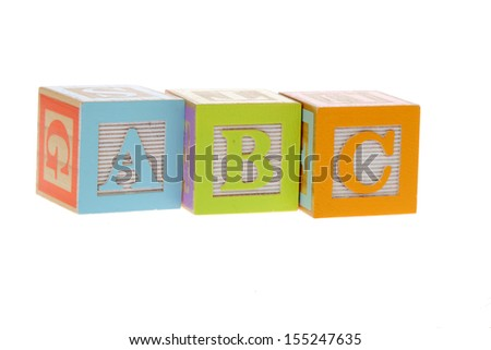 Children's wooden blocks with letters on the study of writing and reading for children/Assorted children's toy letter building blocks against a white background  - stock photo