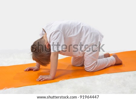Children's yoga. The little boy does exercise. - stock photo