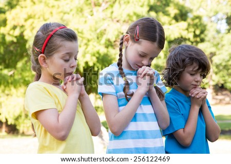 Children saying their prayers in park on a sunny day - stock photo