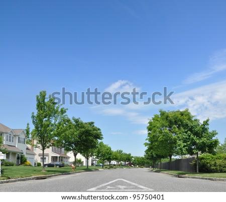 Children School Crossing Traffic Sign on street of Suburban Residential Neighborhood on Beautiful Blue Sky Day - stock photo