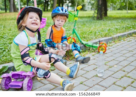 Children scooterists rest sitting on curb of walkway in park, focus on grimacing girl