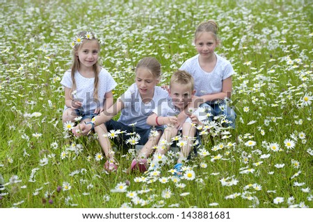 children seated outdoors, in meadow between daisies - stock photo