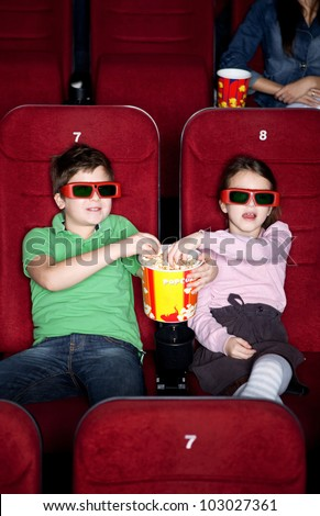 Children sharing popcorn in the 3D movie theater - stock photo