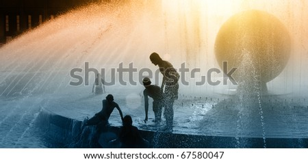 Children silhouettes playing in water fountain at sunset - stock photo