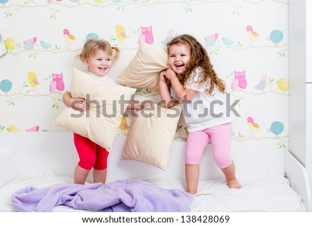 children sisters play on the bed with pillows - stock photo