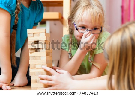 Children - sisters - playing at home with bricks in their room - stock photo