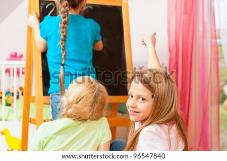 Children - sisters - playing school in their room - stock photo