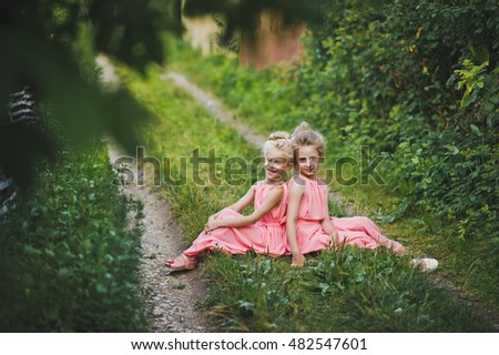 Children sit in the garden on a rustic path.