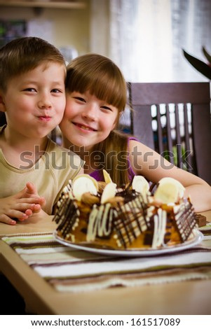 Children sit near a table and eat a cake - stock photo