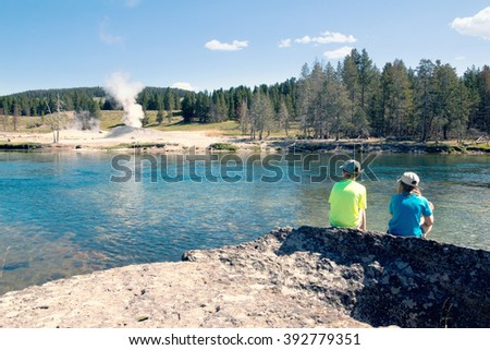 Children sit near the Yellowstone River and look at the steaming geysers. Yellowstone National Park, US - stock photo
