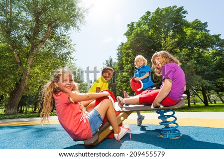 Children sit on playground carousel with springs - stock photo