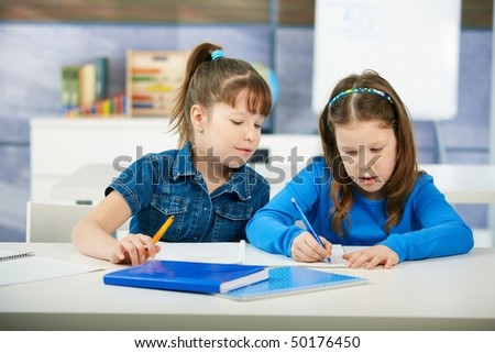Children sitting at desk and learning together in primary school classroom. Elementary age children.