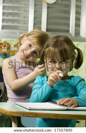 Children sitting at desks in a classroom.  They are smiling and are facing the camera.  Vertically framed shot. - stock photo