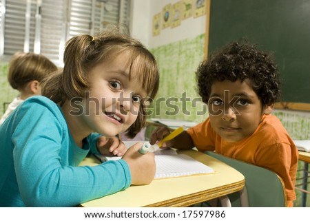 Children sitting at desks in a classroom.  They are working together and are facing the camera.  Horizontally framed shot.