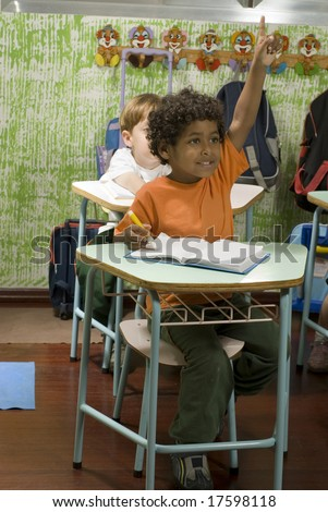 Children sitting at their desks in a classroom.  A boy has his hand raised and is smiling.  Vertically framed shot.