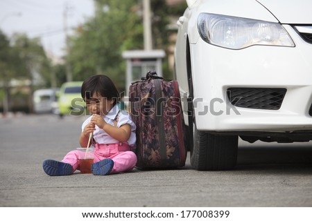 children sitting beside passenger car wheel and drinking beverage by plastic tube with happy face