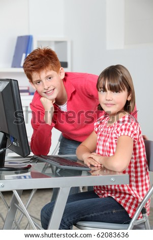 Children sitting in classroom in front of computer - stock photo