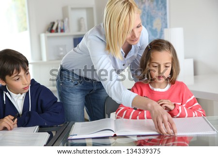 Children sitting in classroom with teacher - stock photo