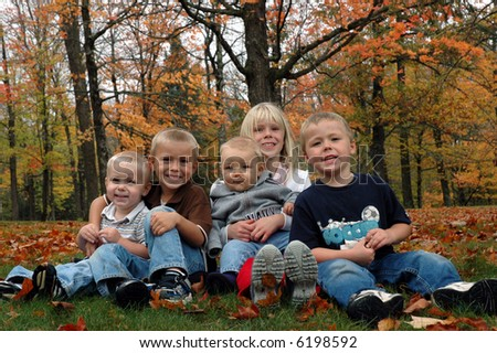 children sitting in fall leaves - stock photo