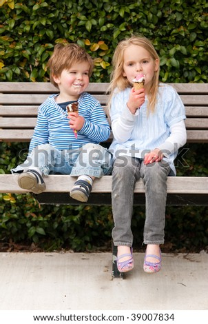 Children sitting in park eating ice-cream - stock photo