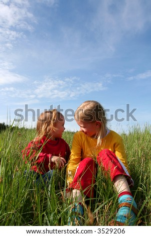 Children sitting in the grass on a blue sky background