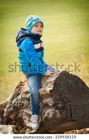 Children sitting on an old trunk in the park - stock photo