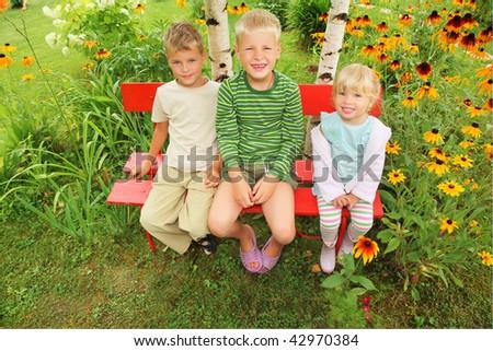 Children sitting on bench in garden - stock photo