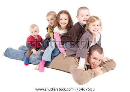 Children sitting on mans back on floor - stock photo
