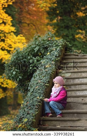 Children sitting on old stone stairs in the park - stock photo