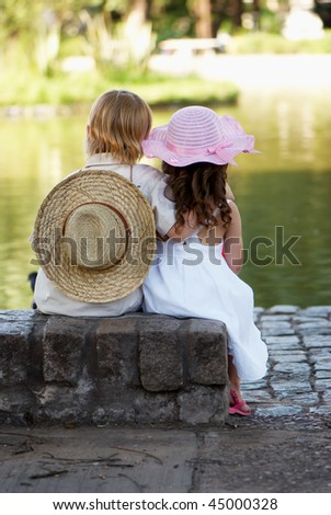 Children sitting on the bank of lake in park - stock photo