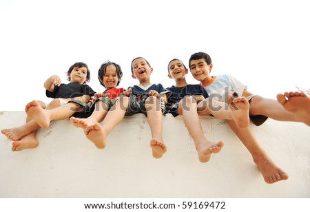 Children sitting on wall, happy boys laughing - stock photo