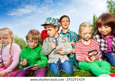 Children sitting with magnifier and writing notes - stock photo