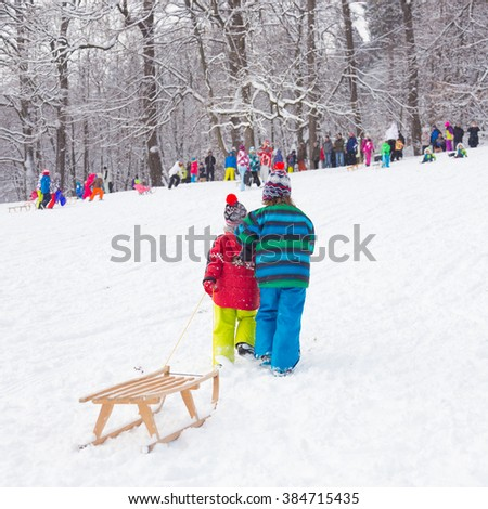 Children sledding and having fun on first winter snow.