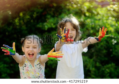 Children soiled with paint, having fun and show his dirty hands to the camera. Child has fun and painting / drawing. Children's creativity. Art for baby. Emotions. Children playing. Delight. - stock photo