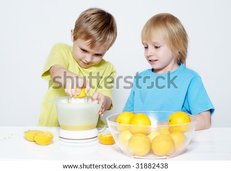Children squeeze out orange juice - stock photo