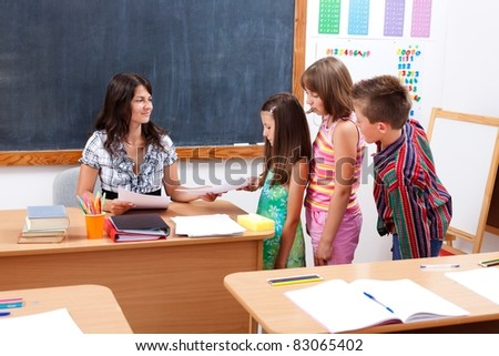 Children standing in row in front of teacher who gives or receives test paper - stock photo