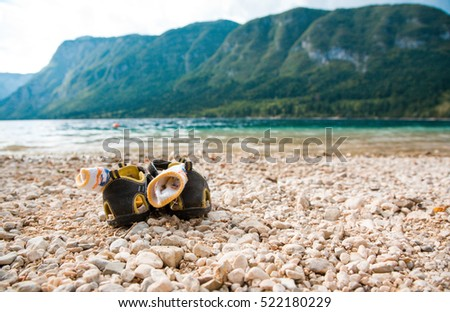 children summer shoes, sandals with socks on the lake shore