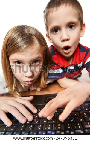 Children surprise and emotional look at the laptop screen - stock photo