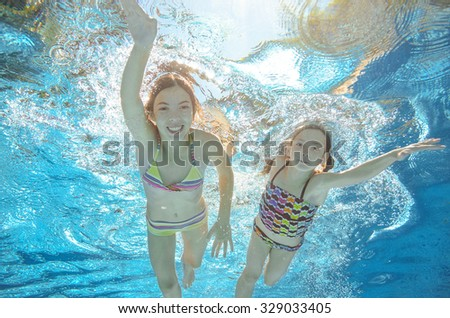 Children swim in pool or sea underwater, happy active girls have fun in water, kids sport on family vacation  - stock photo