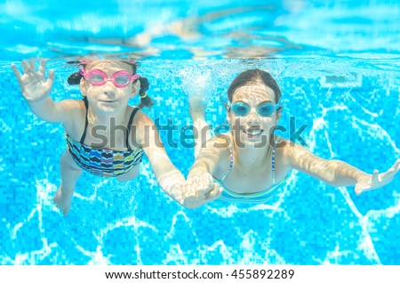 Children swim in pool under water, happy active girls in goggles have fun, kids sport on active family vacation  - stock photo