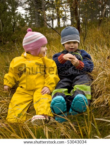 Children talking together in an autumn forest - stock photo