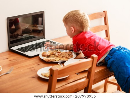 Children, technology and home concept  - little boy child eating meal while using laptop pc computer at home. Bad habits - stock photo