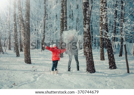 Children throwing snow in the air on sunny day in snowy forest. Kids outdoors in winter. Sisters playing in snow. Family winter vacations. Toned image.  - stock photo