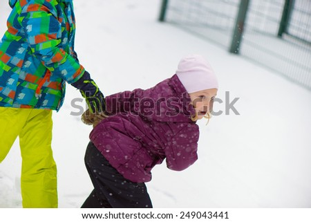 Children throwing snowballs in snowy winter park - stock photo