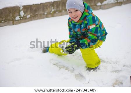 Children throwing snowballs in snowy winter park - stock photo