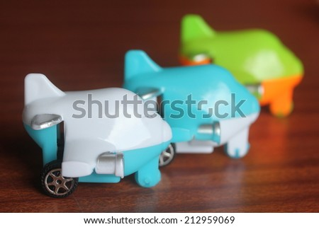 children toy plane or airplane or aeroplane placed next to each other on a wooden table  - stock photo