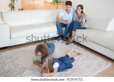Children using a tablet computer while their happy parents are watching in their living room - stock photo